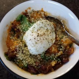 Vegan chili - topped with spinach and a poached egg, sprinkled and with hemp seed