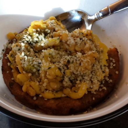 Veggie burger topped with lemony yellow lentils and hemp seeds.