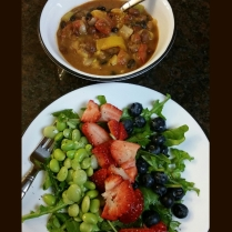 Arugula dressed in olive oil, lemon juice and balsamic topped with fresh strawberries, blueberries, and blend of edamame and limabeans with a bowl of vegan chili