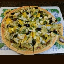 Vegan pizza with an avocado sauce topped with onions, yellow tomatoes, kalamata olives, artichokes, and mustard greens.