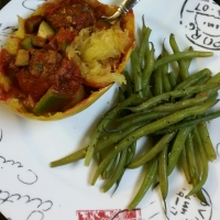 Baked spaghetti squash bowls with vegan neatballs and sweet pepper and onion pasta sauce with a side of steamed green beans