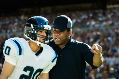 Professional football coach motivating player on sidelines crowded stadium in background