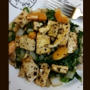 Sauteed tofu atop bok choy, sprinkled with black sesame seeds and clementines.