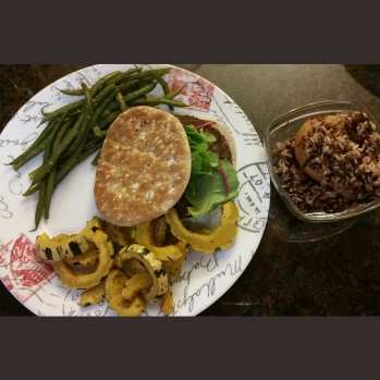 Veggie burger and lettuce between Sandwich Skinnys Bread with a side of green beans and baked delicata squash. Alongside, a bowl with cinnamon baked pear topped with a wild rice blend.